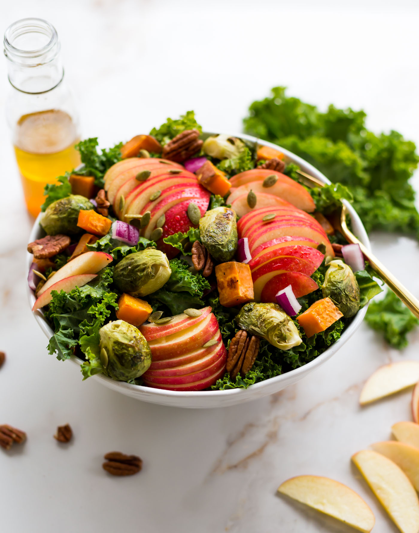 Fall Kale Salad with apples, brussel sprouts, sweet potato, pecans, pumpkin seeds, and purple onions in a white salad bowl.