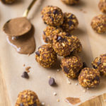 No bake pumpkin energy bites on wax paper on top of cutting board with spoon of almond butter