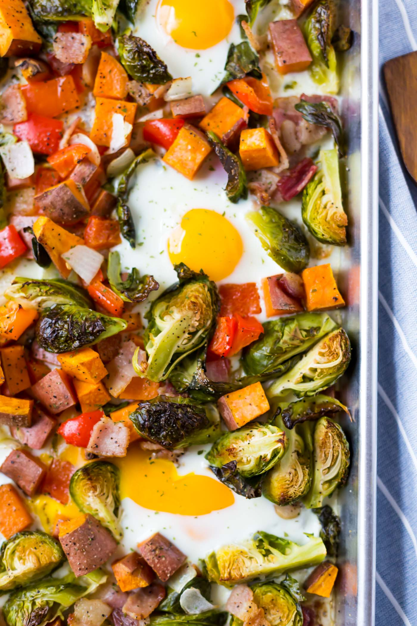 Brussels sprouts, sweet potato, bacon, bell peppers, onions, and eggs baked on a sheet pan.