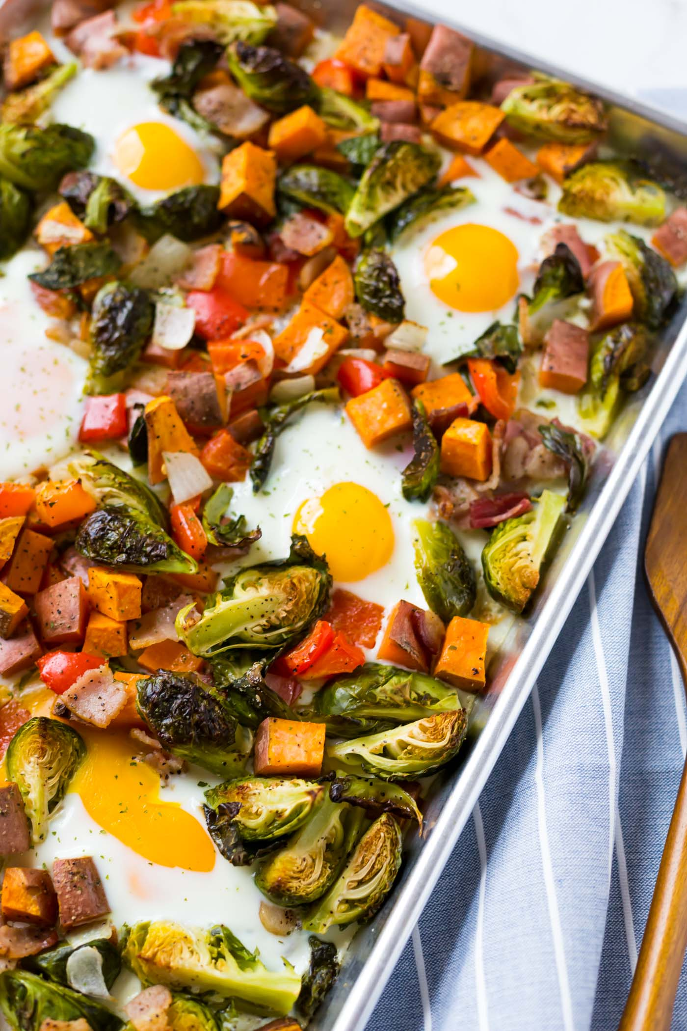 Eggs, brussel sprouts, sweet potatoes, bacon, and bell peppers combined on sheet pan.