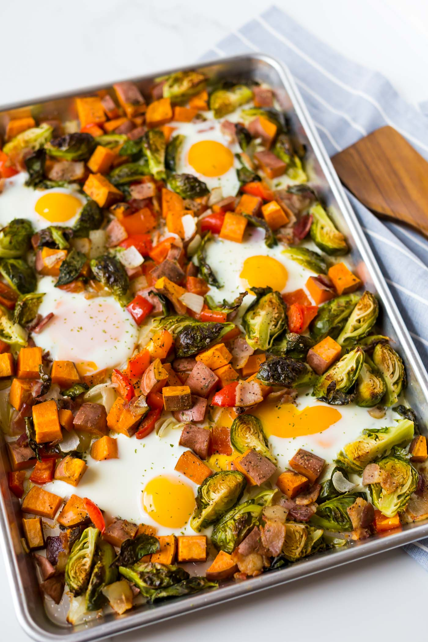 Eggs, bacon, sweet potatoes, brussel sprouts, onion, and red bell pepper on sheet pan with wooden spatula and blue towel with white stripes.