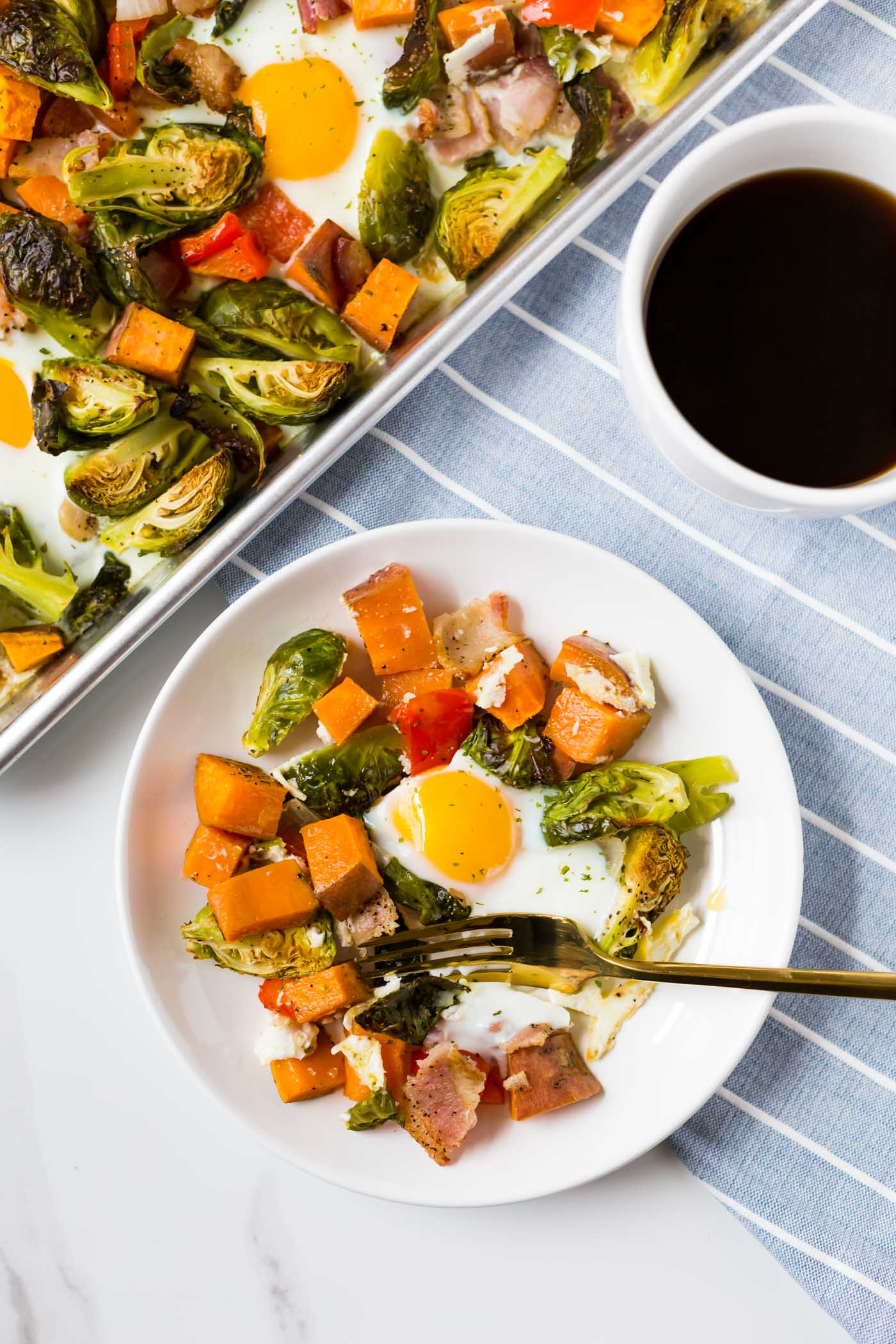 white plate with one egg, brussel sprouts, sweet potato, bacon, and a red bell pepper.