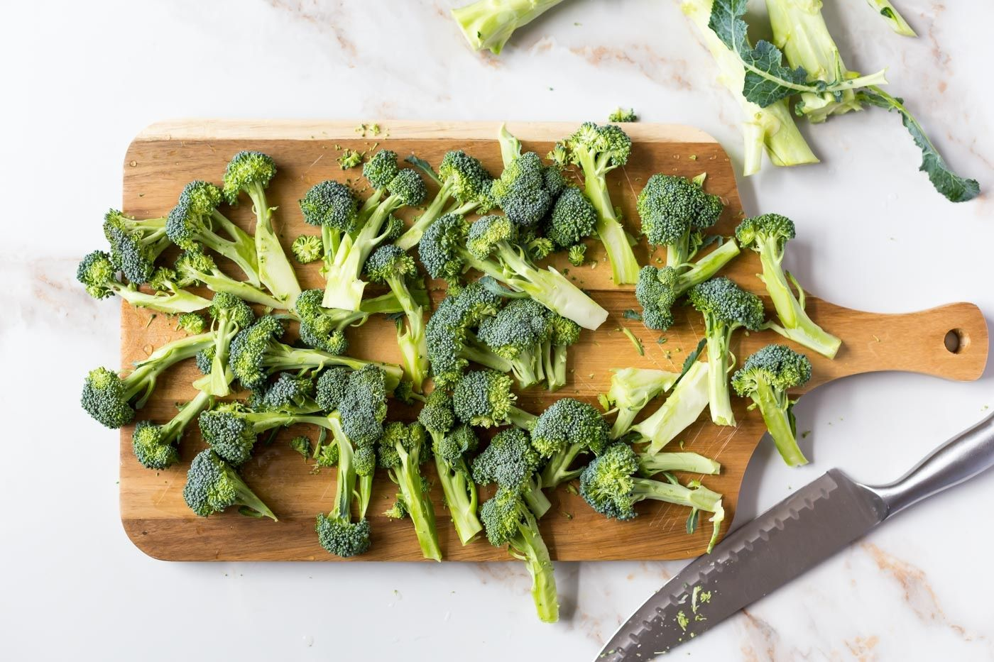 broccoli florets chopped up on cutting board