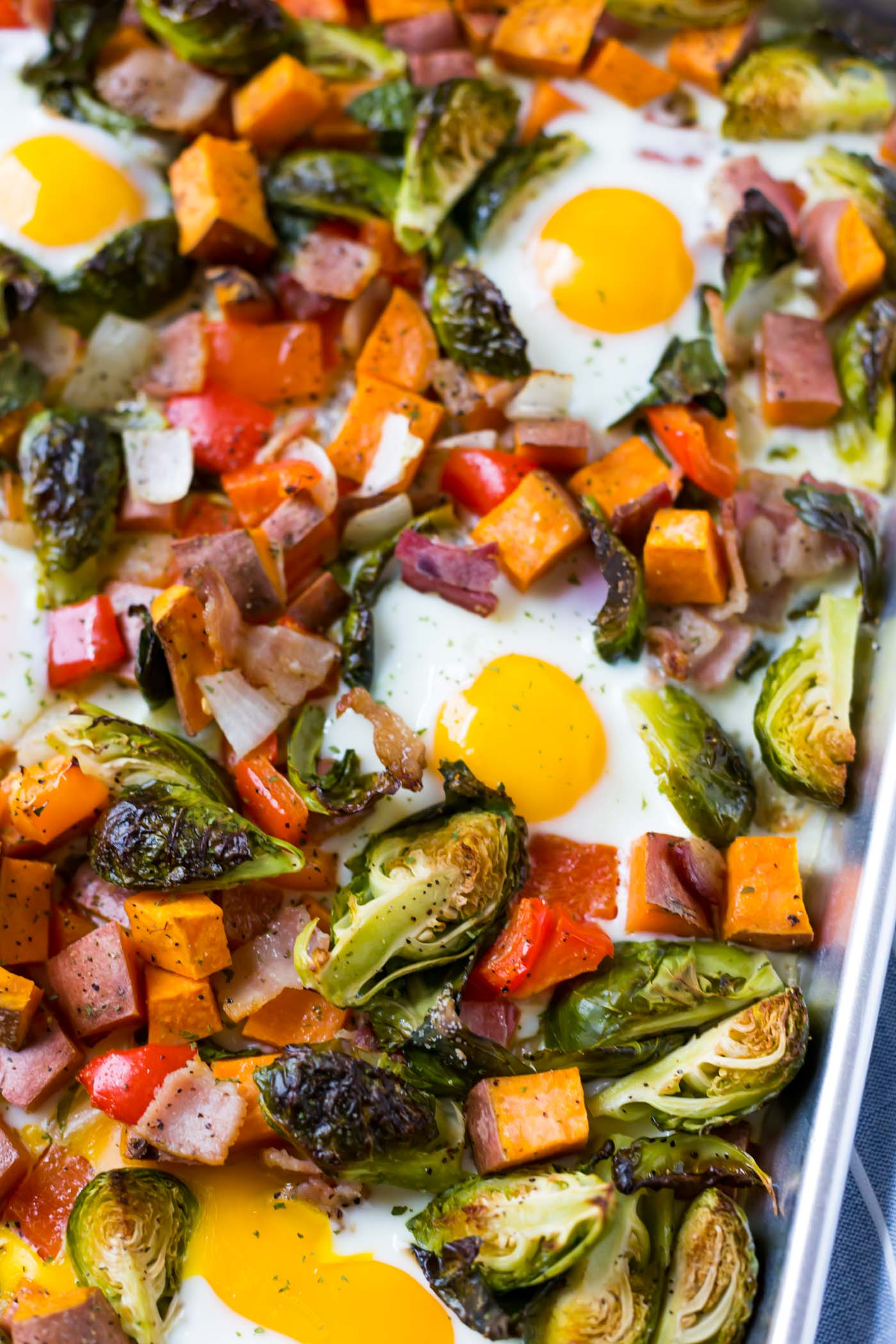 breakfast hash on sheet pan with sweet potatoes, eggs, bacon, brussel sprouts, and red bell pepper.