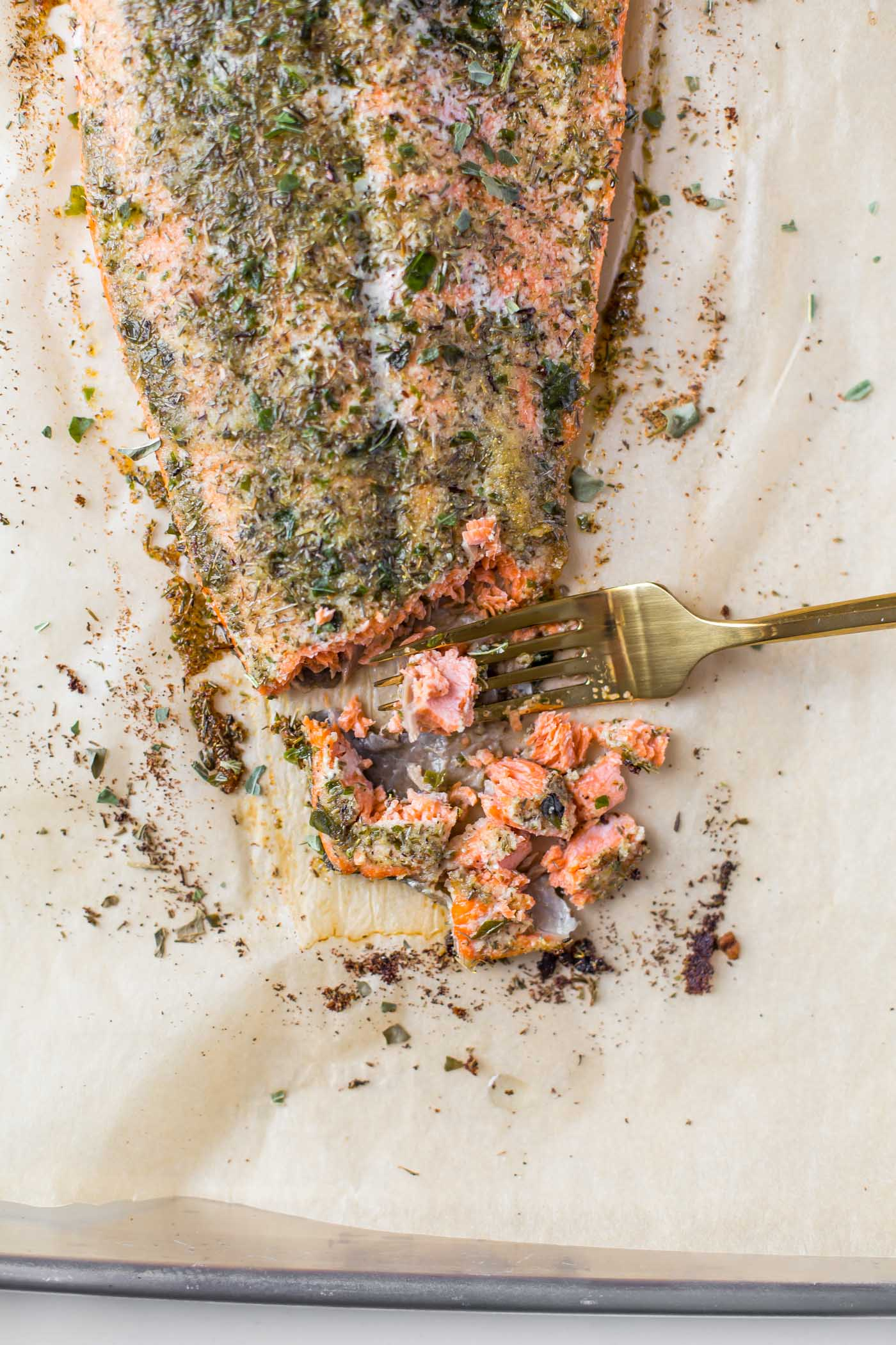 baked salmon fillet with gold fork pulling apart salmon