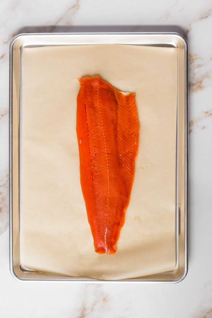 raw salmon fillet on parchment paper on baking sheet on white background
