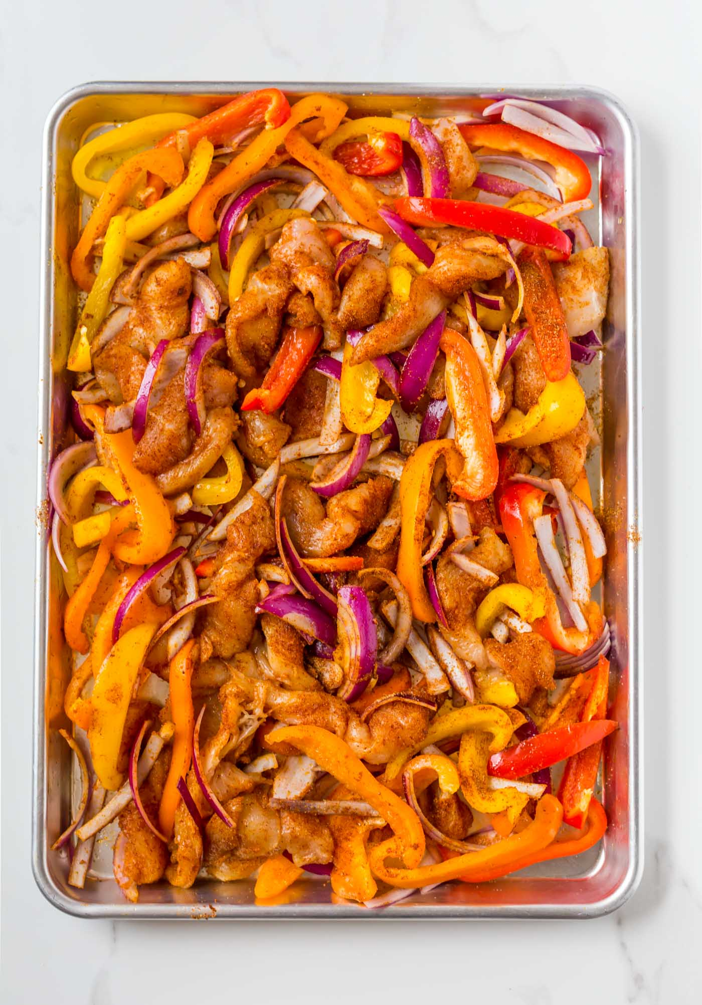 raw chicken fajitas with seasoned chicken, red, orange, and yellow bell peppers, and red onions on sheet pan