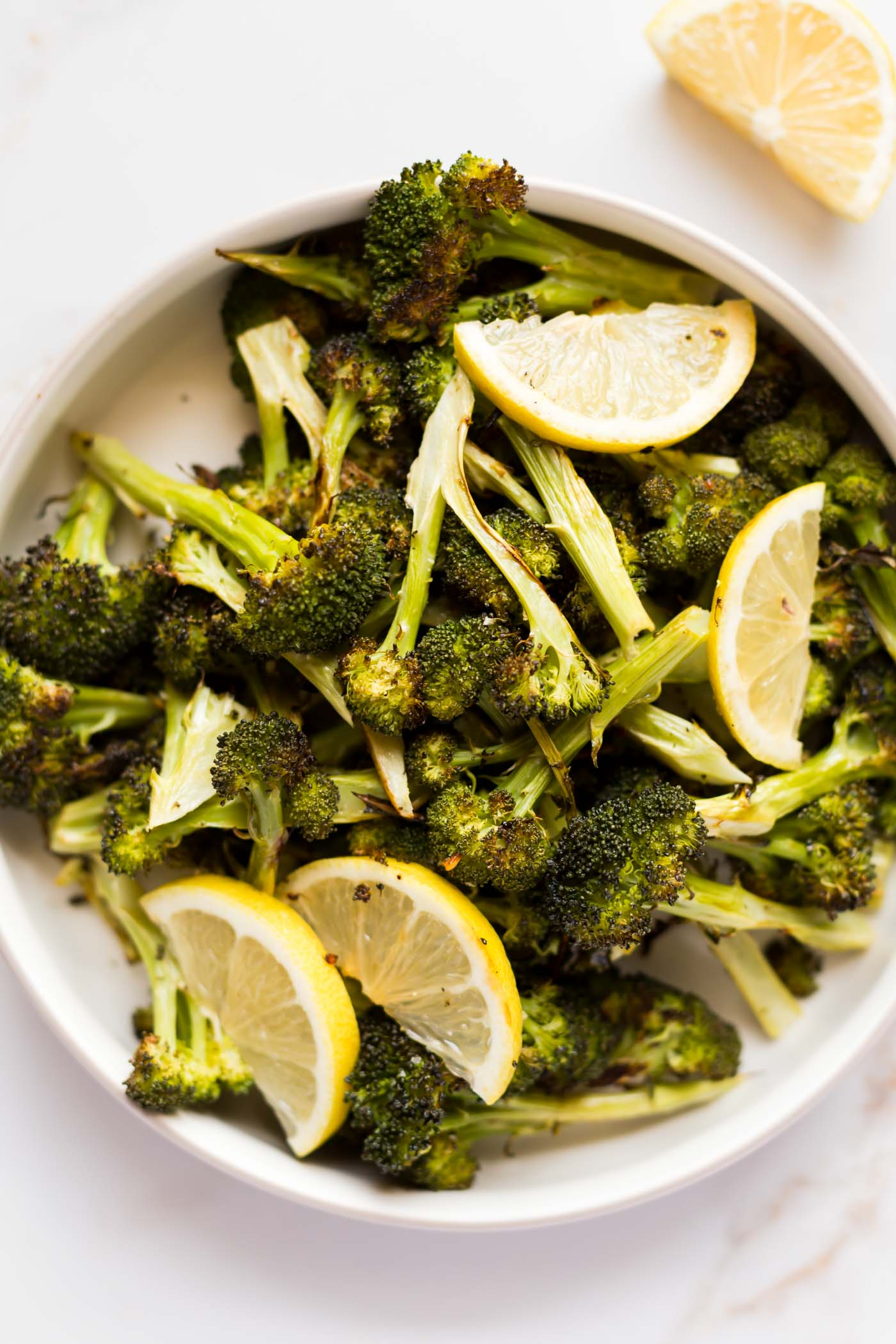 Roasted Broccoli and lemons in white bowl