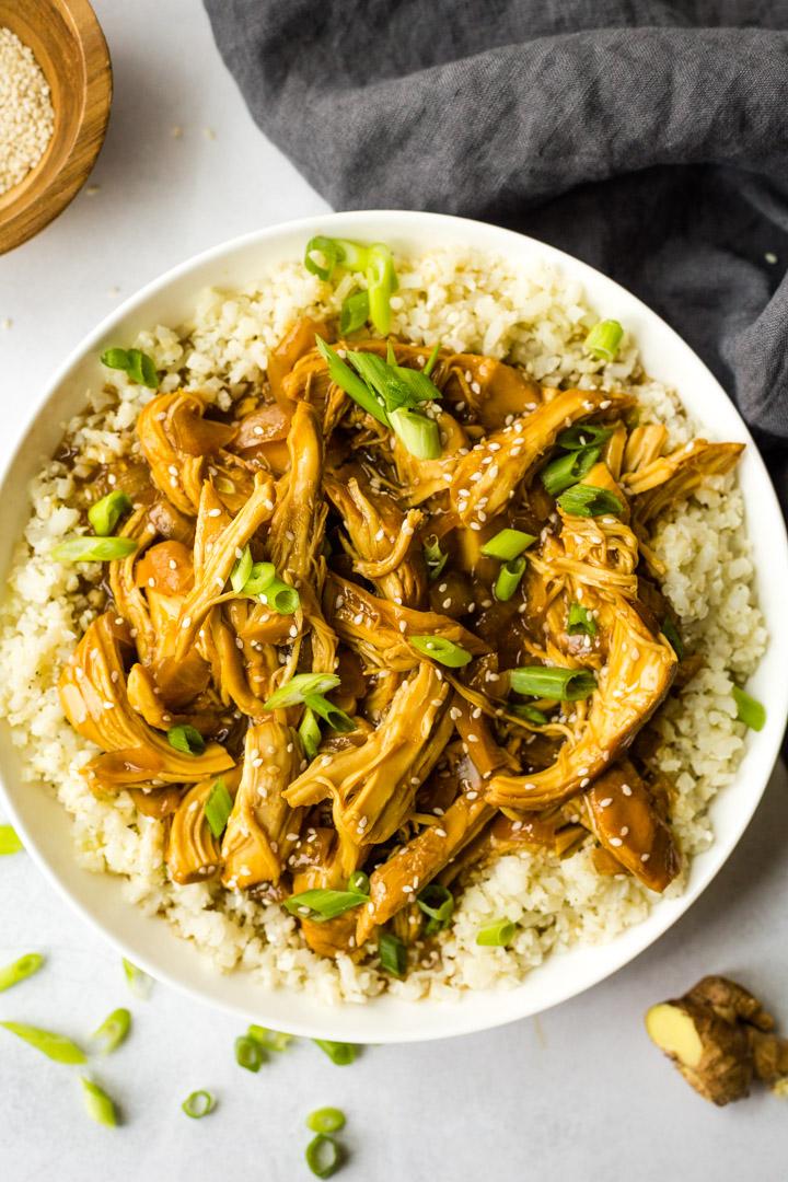 Slow cooker teriyaki chicken served over cauliflower rice in white bowl
