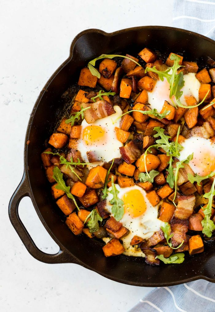 Cast iron skillet filled with sweet potatoes, eggs, and bacon. Topped with arugula