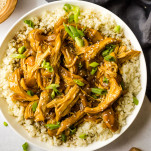 Teriyaki chicken served over cauliflower rice in white bowl