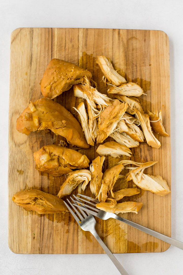 Two forks with shredded chicken on cutting board