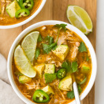 Two white bowls filled with chicken, white beans, broth, limes, jalapenos, and diced avocado