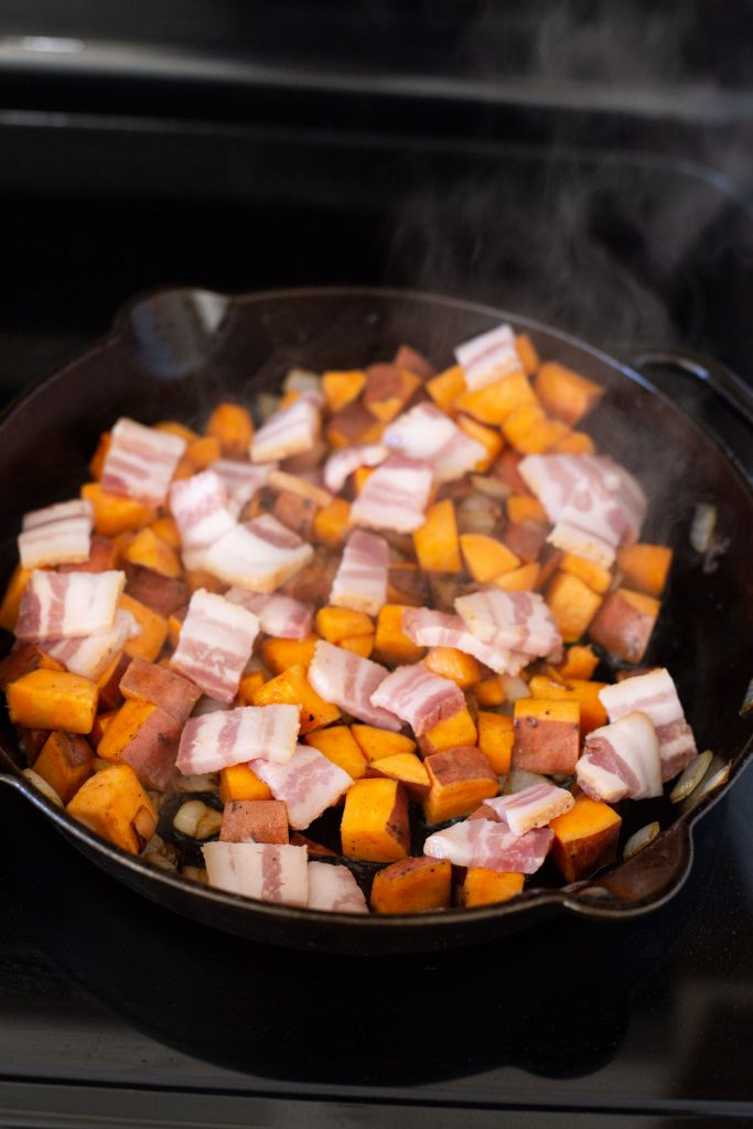 Cooking sweet potatoes and bacon on cast iron skillet