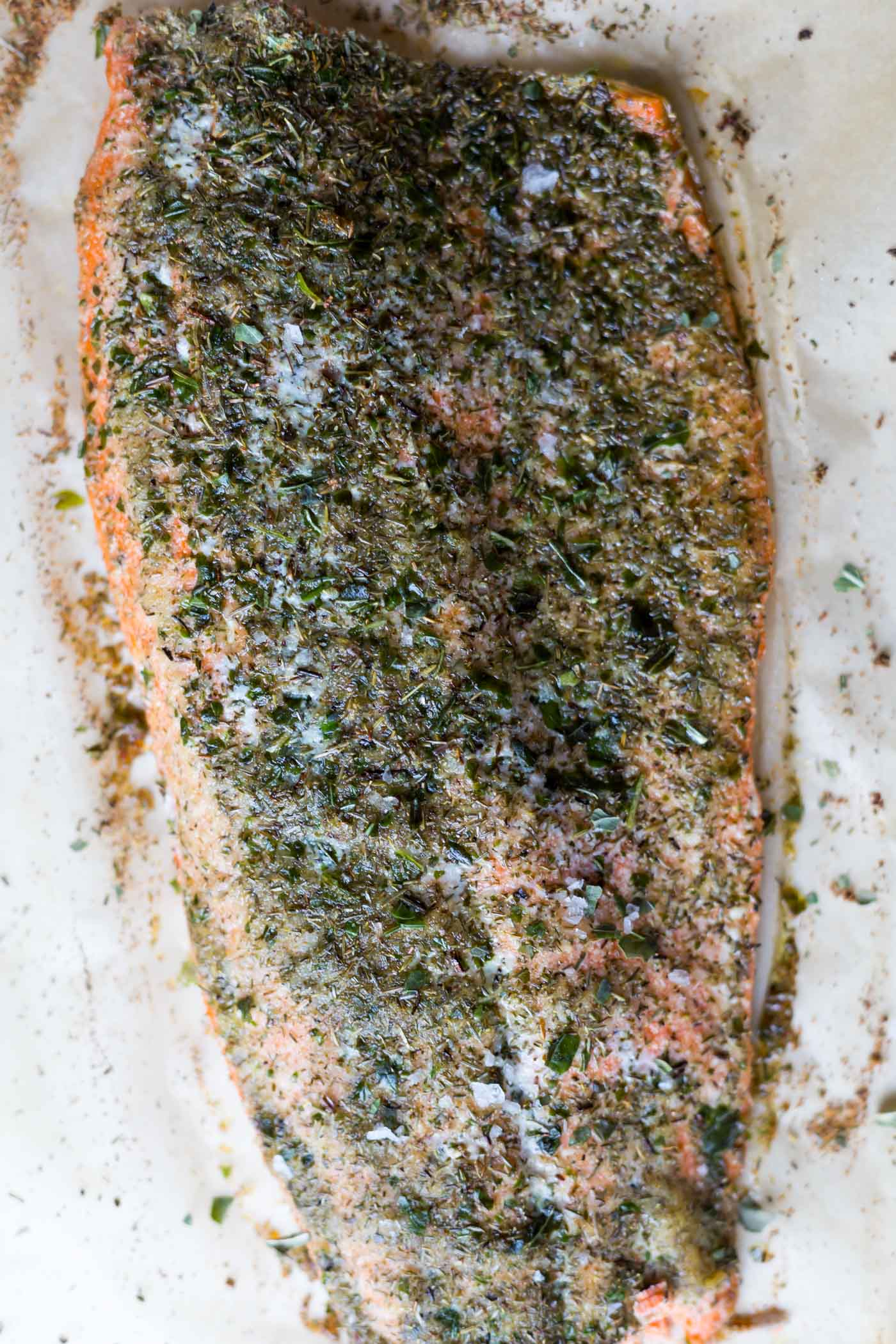 Oven baked salmon fillet on parchment paper with herbs and seasonings
