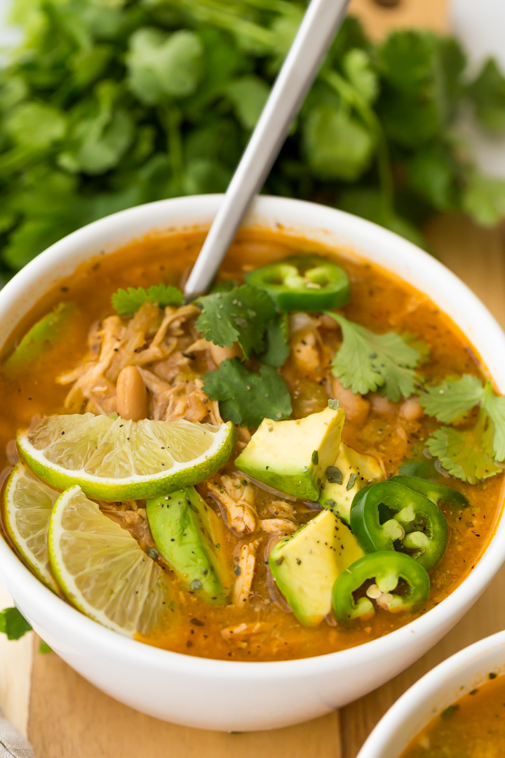 bowl of white chicken chili garnished with cilantro, avocado, and jalapenos