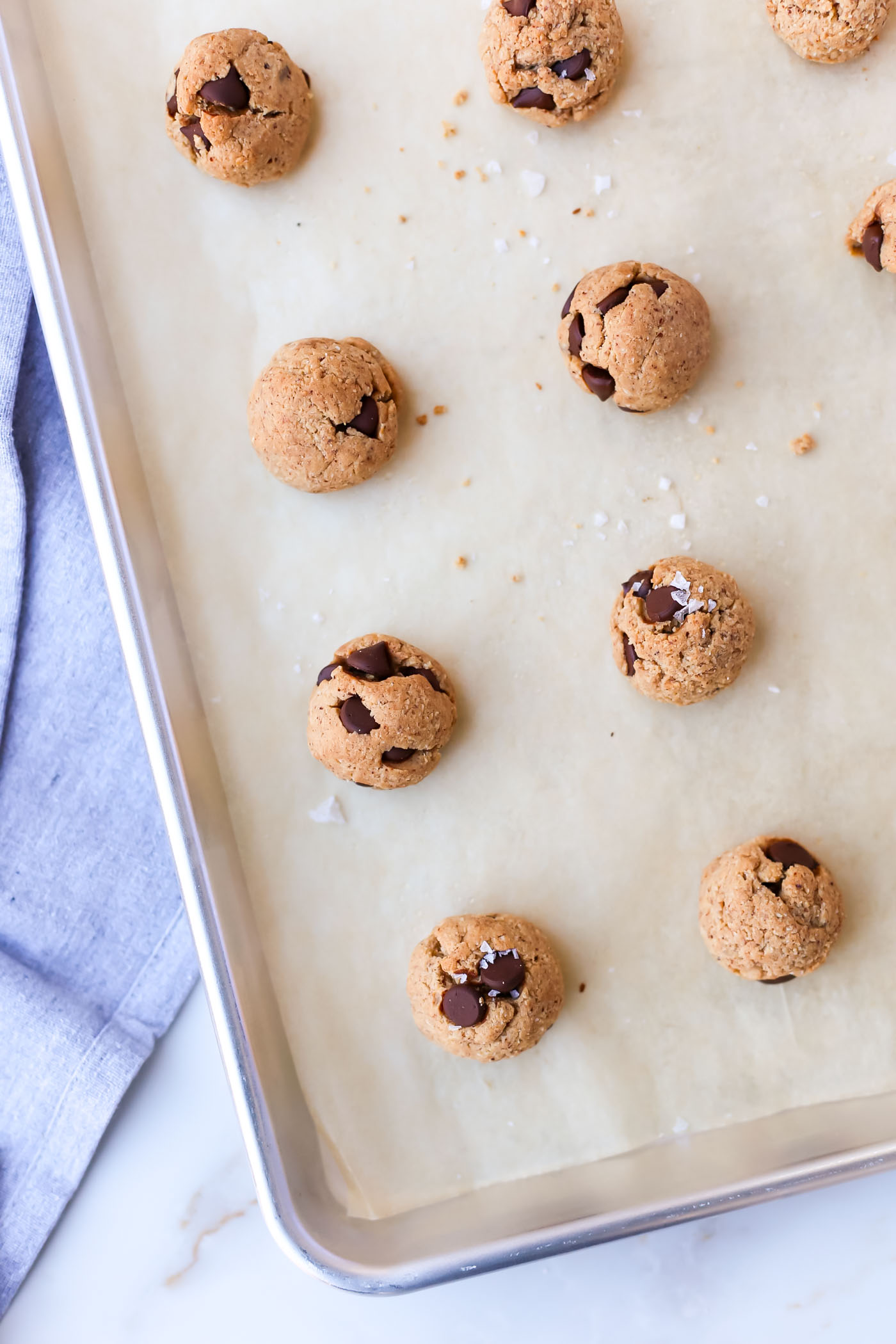 rows of chocolate chip cookies on sheet pan with blue napkin on the side