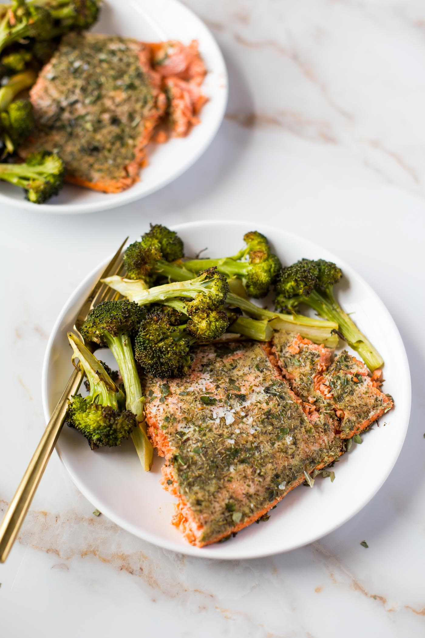 Two white plates with baked salmon and roasted broccoli on white background