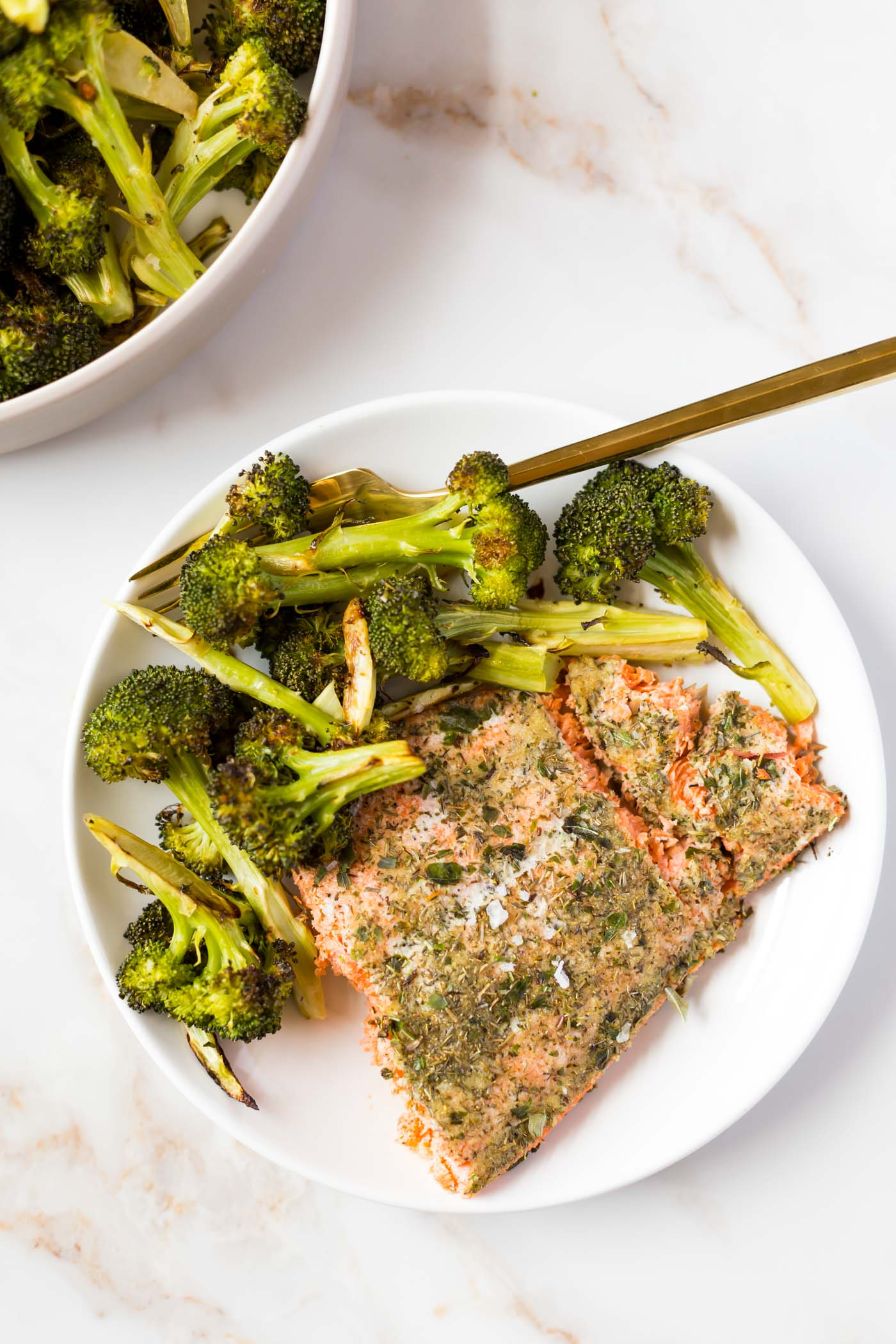 Baked salmon with roasted broccoli on white plate and roasted broccoli in corner