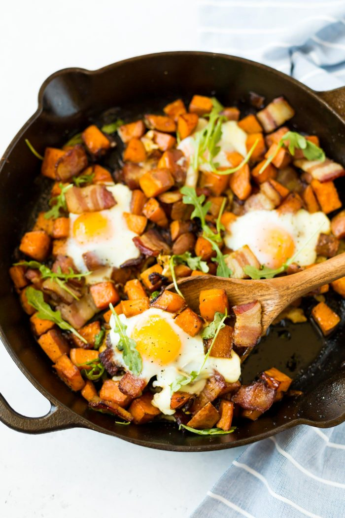 Wooden spatula scooping out sweet potato breakfast hash.