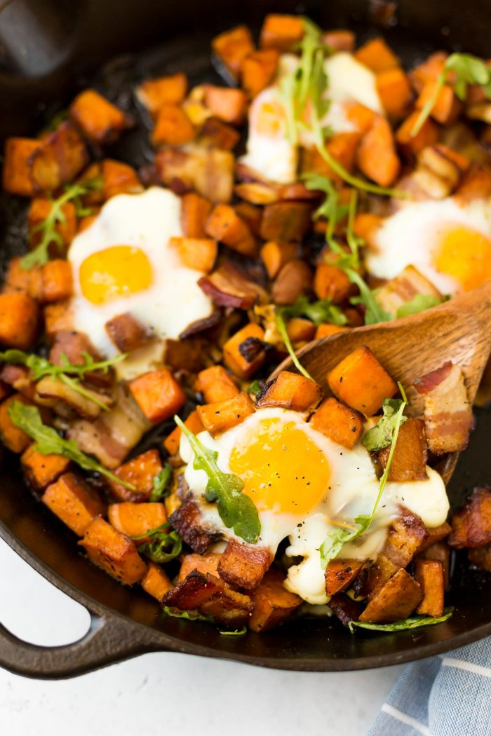Wooden spatula scooping out egg, sweet potato and bacon from cast iron skillet.
