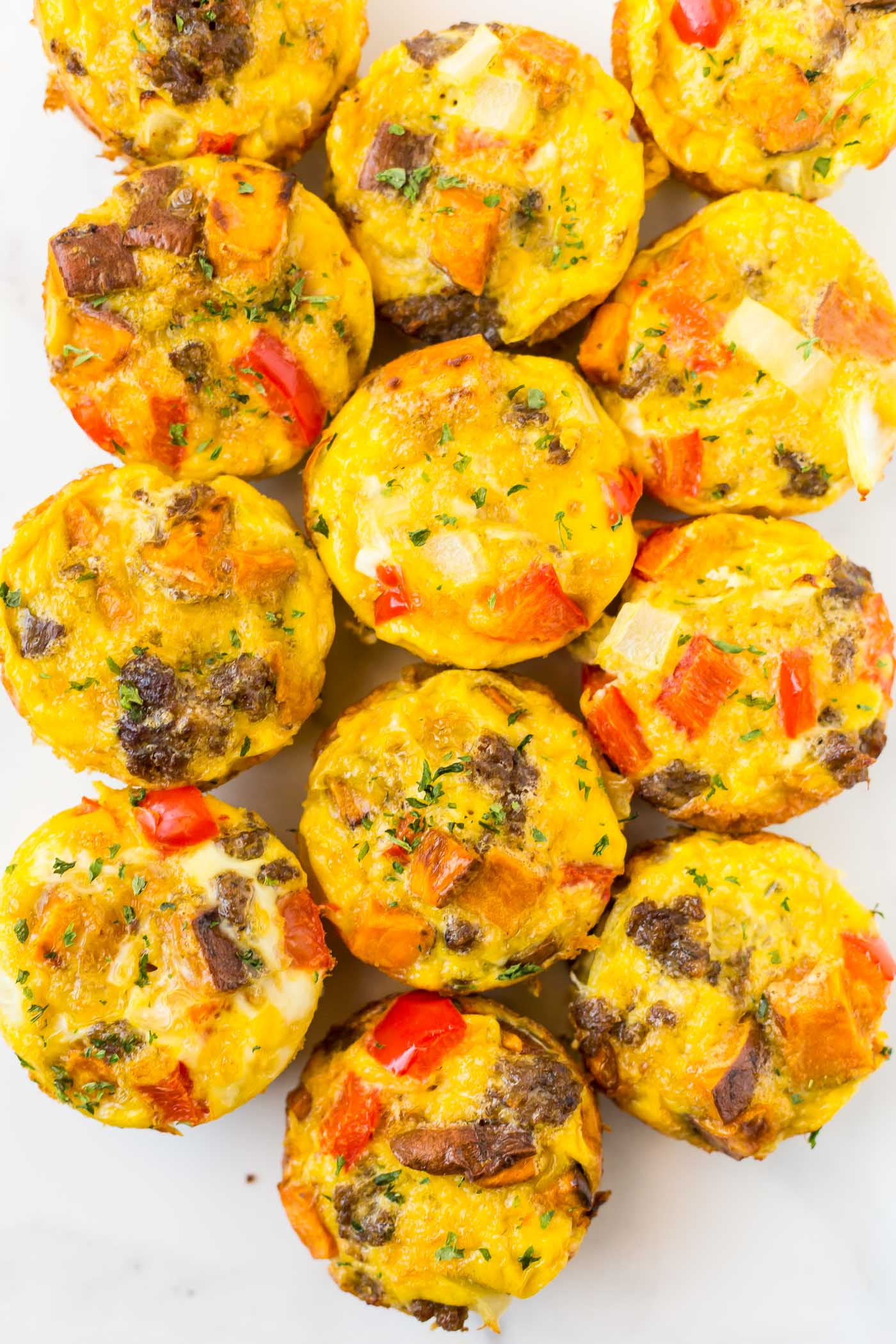 Baked egg breakfast muffins in a row on white background