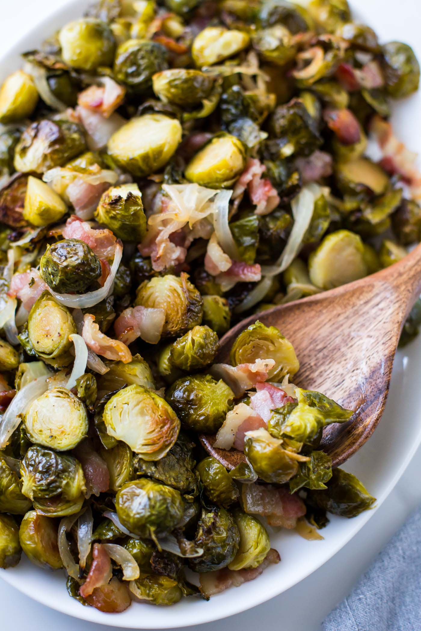 Maple roasted brussels sprouts with bacon on a white plate with a wooden spoon