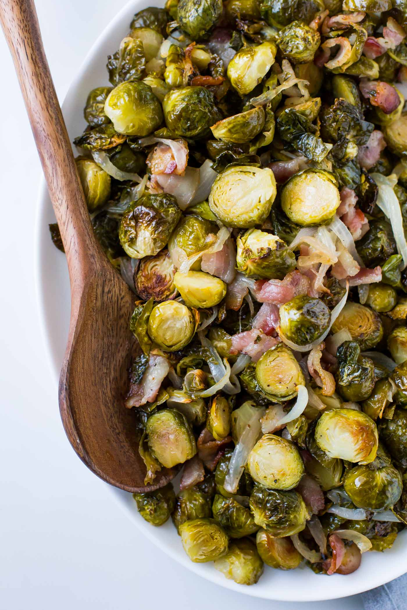 Maple roasted brussels sprouts with bacon, and onions on a white plate with a wooden spoon