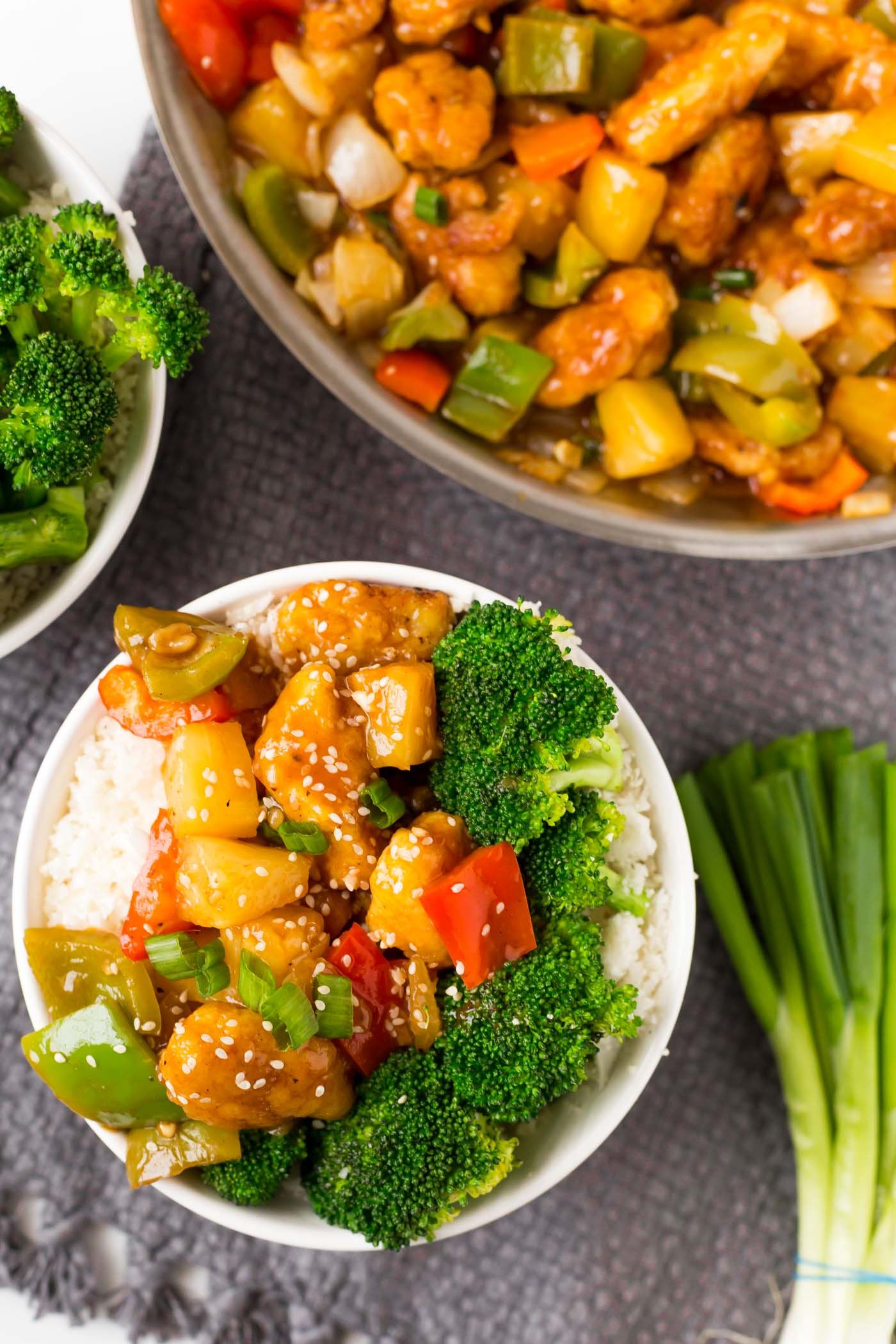 white bowl filled with sweet and sour chicken, broccoli, and cauliflower rice and skillet of sweet and sour chicken in corner