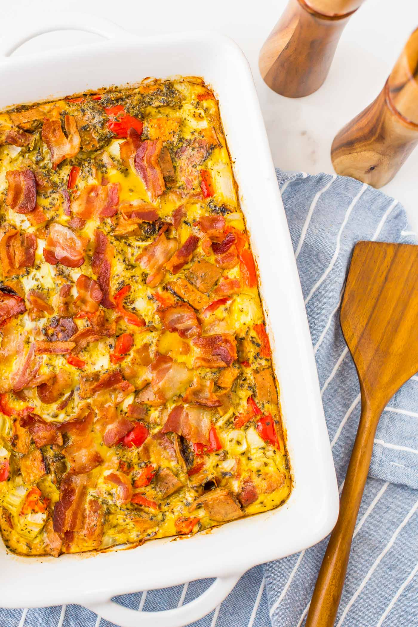 Breakfast casserole with bacon on top in white casserole dish on blue napkin with wooden spatula
