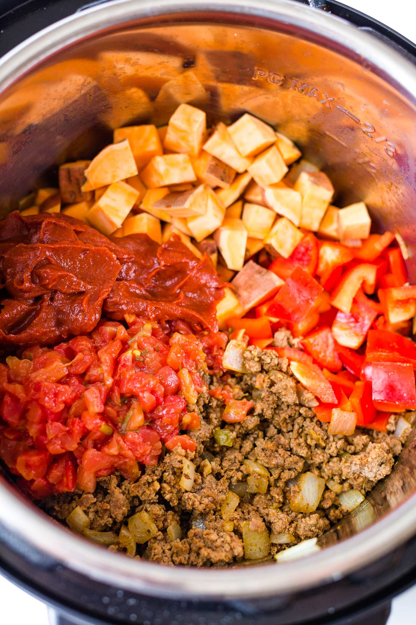 Diced sweet potatoes, diced tomatoes, ground beef, bell pepper and tomato paste in instant pot