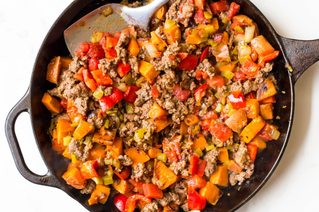 Mixed sweet potatoes, breakfast sausage, bell pepper, diced green chiles and diced tomatoes in cast iron skillet