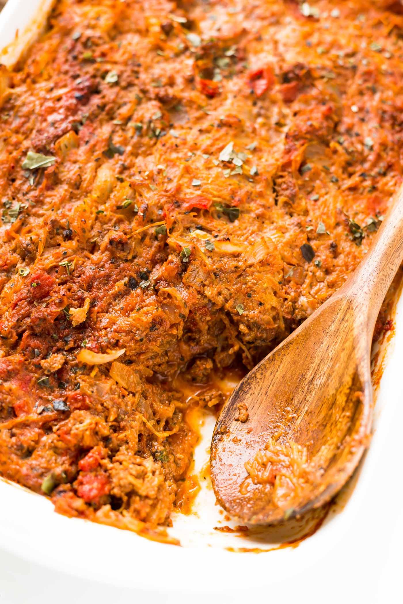 Spaghetti squash and wooden spoon in white casserole dish