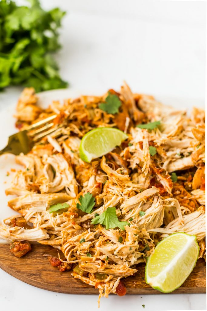 Shredded mexican chicken garnished with cilantro and sliced limes on cutting board