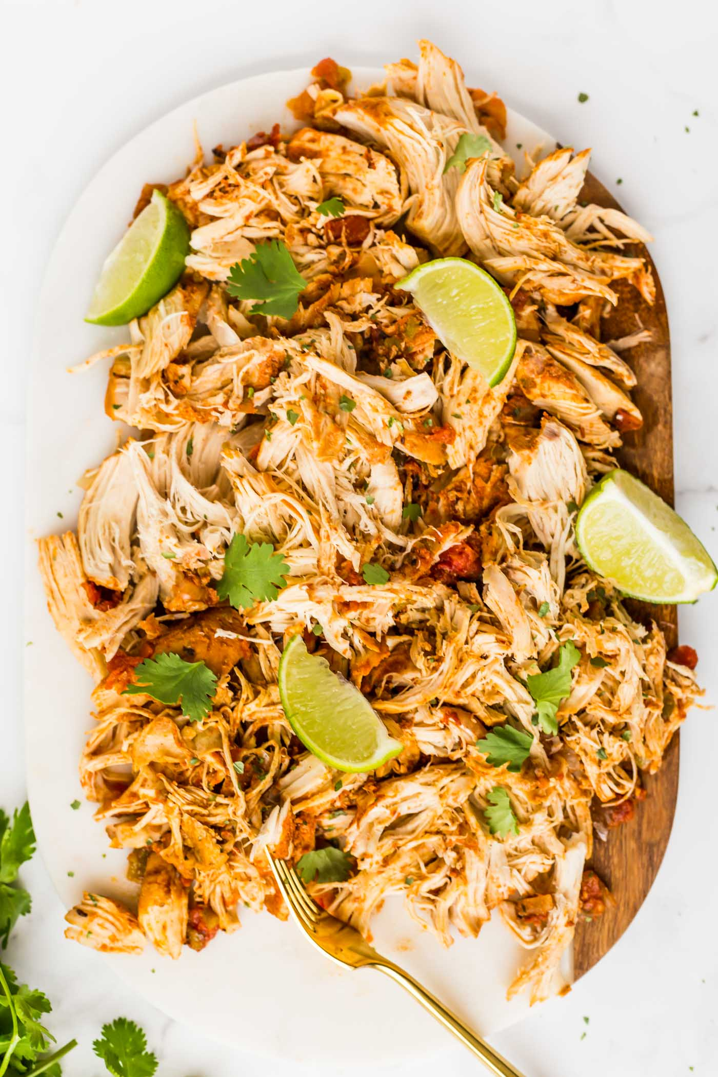 Shredded Mexican Chicken Garnished with Cilantro and sliced limes on cutting board on top of white background