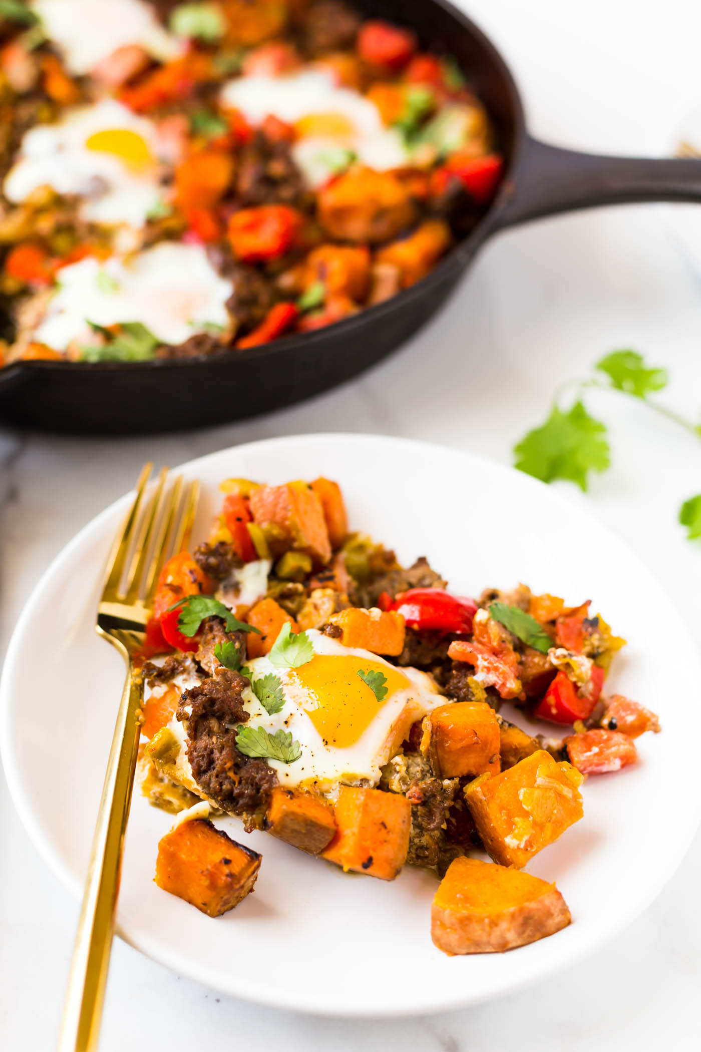 Sweet potato breakfast hash with sausage on white plate with gold fork in front of cast iron skillet
