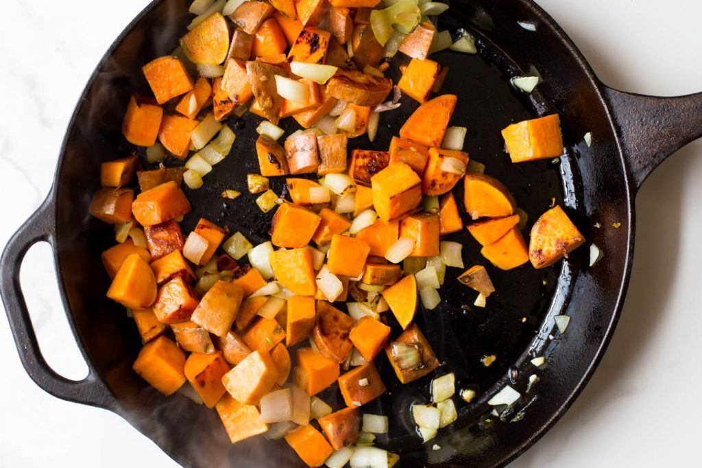 Sweet potato, onion, and garlic sauteing in cast iron skillet