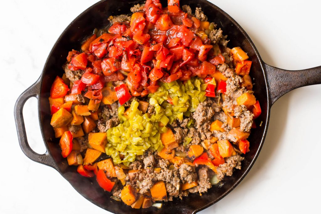 Sweet potatoes, breakfast sausage, bell pepper, diced green chiles and diced tomatoes in cast iron skillet