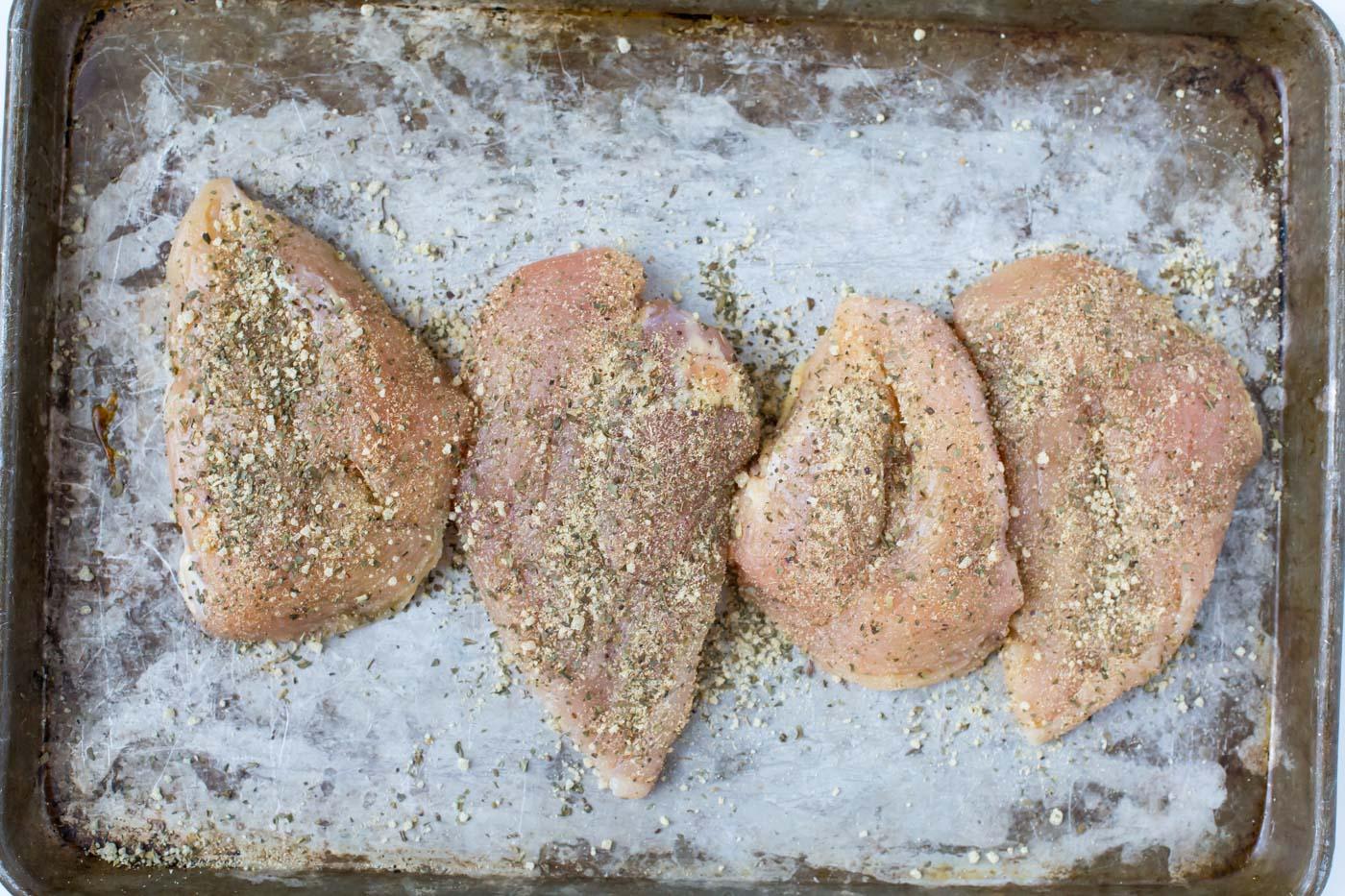 seasoned raw chicken breast on baking sheet