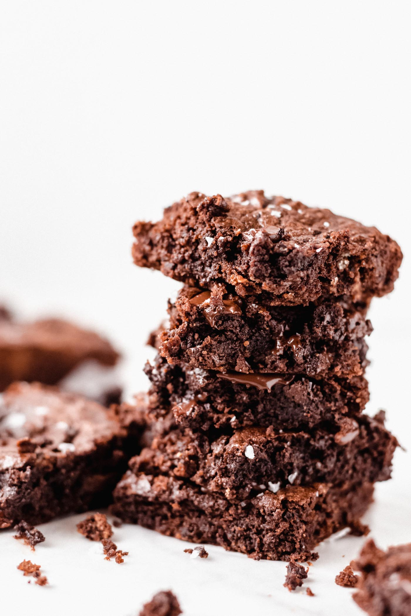 Stacked paleo brownies with scattered brownie crumbs and brownies on white background