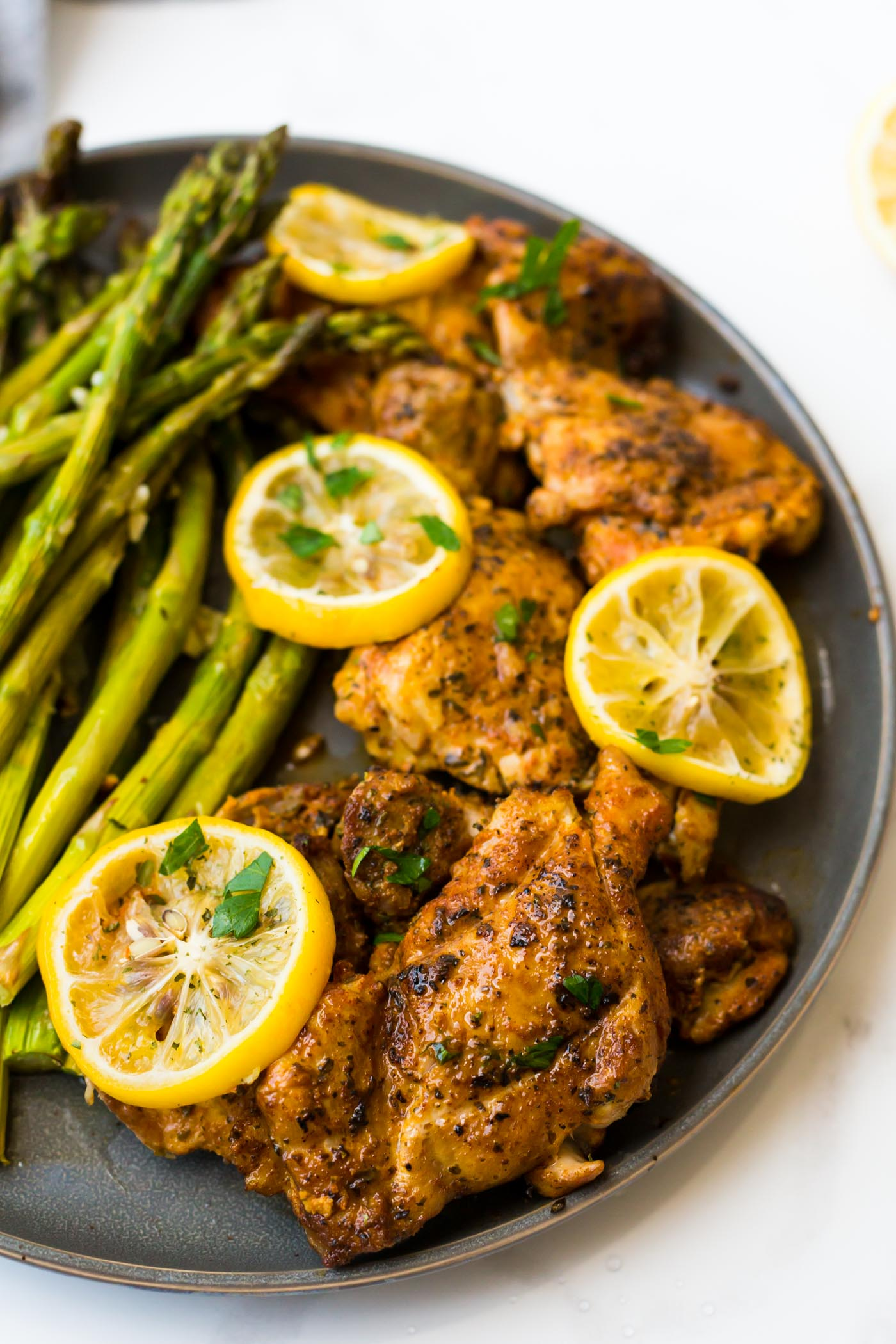 chicken thighs, sliced lemons, and asparagus on a grey plate on white background