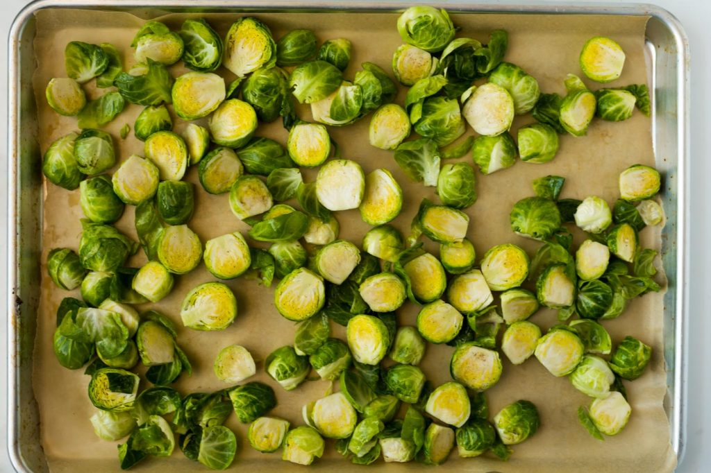 halved brussels sprouts on a piece of parchment paper on a baking sheet