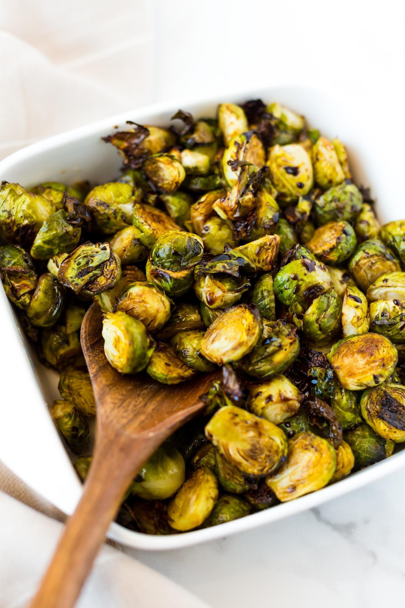 roasted balsamic brussels sprouts in white dish with wooden spoon