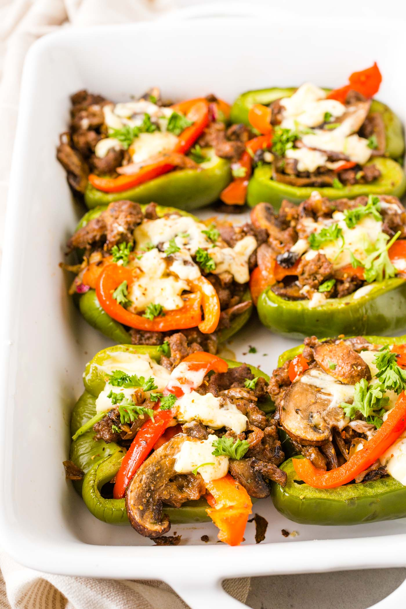 Baked green peppers with ground beef, mushrooms, onions and mayonnaise in white casserole dish