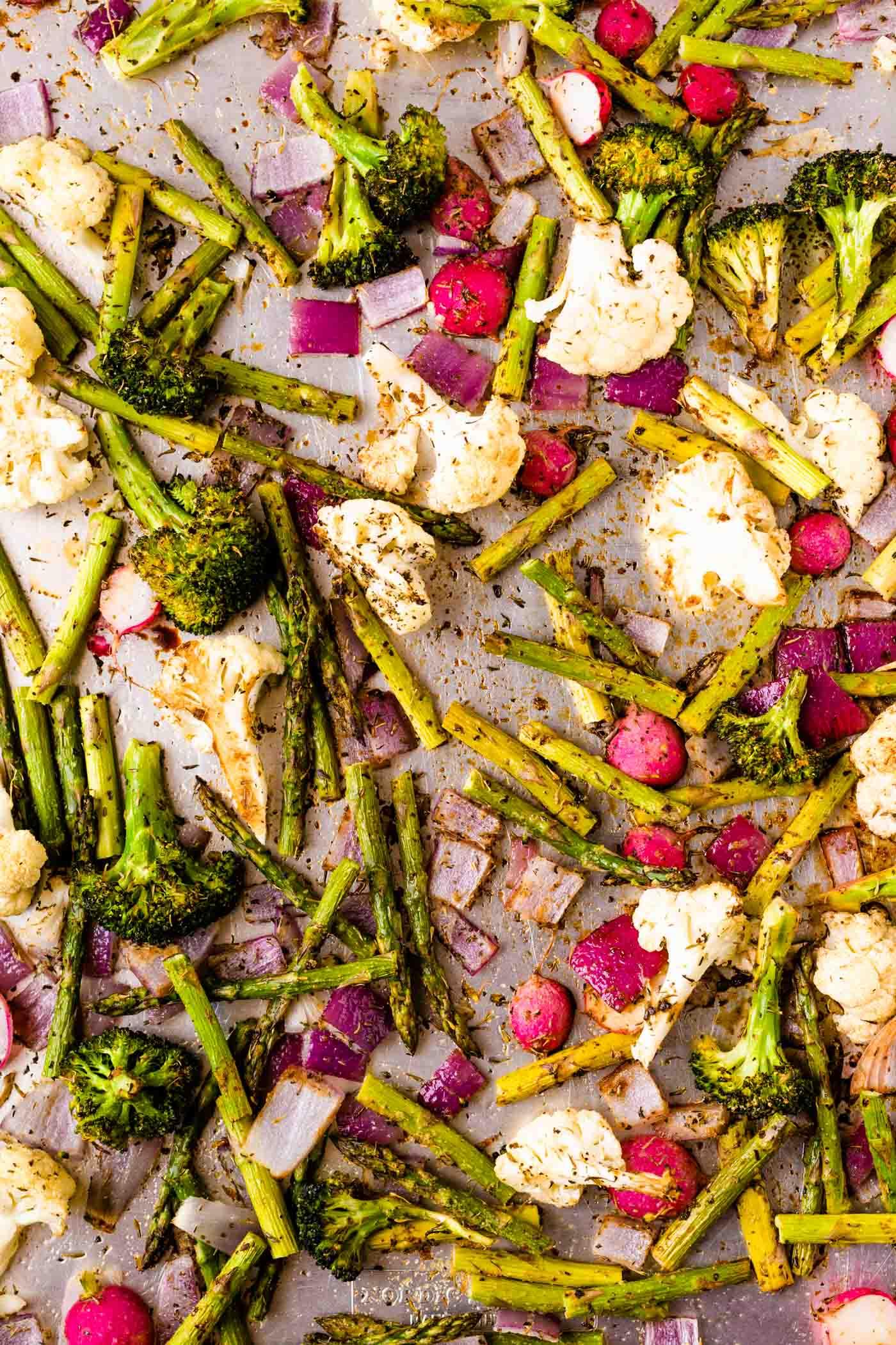 broccoli, cauliflower, asparagus, radishes, and red onion on sheet pan