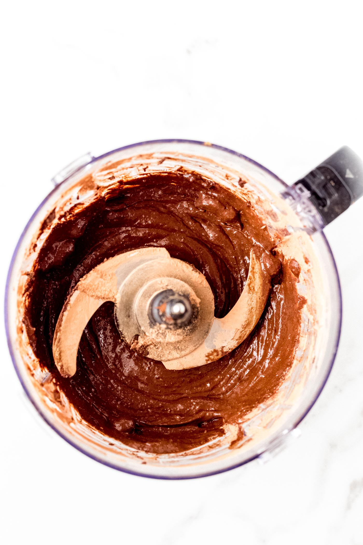 Chocolate brownie batter in food processor on white background
