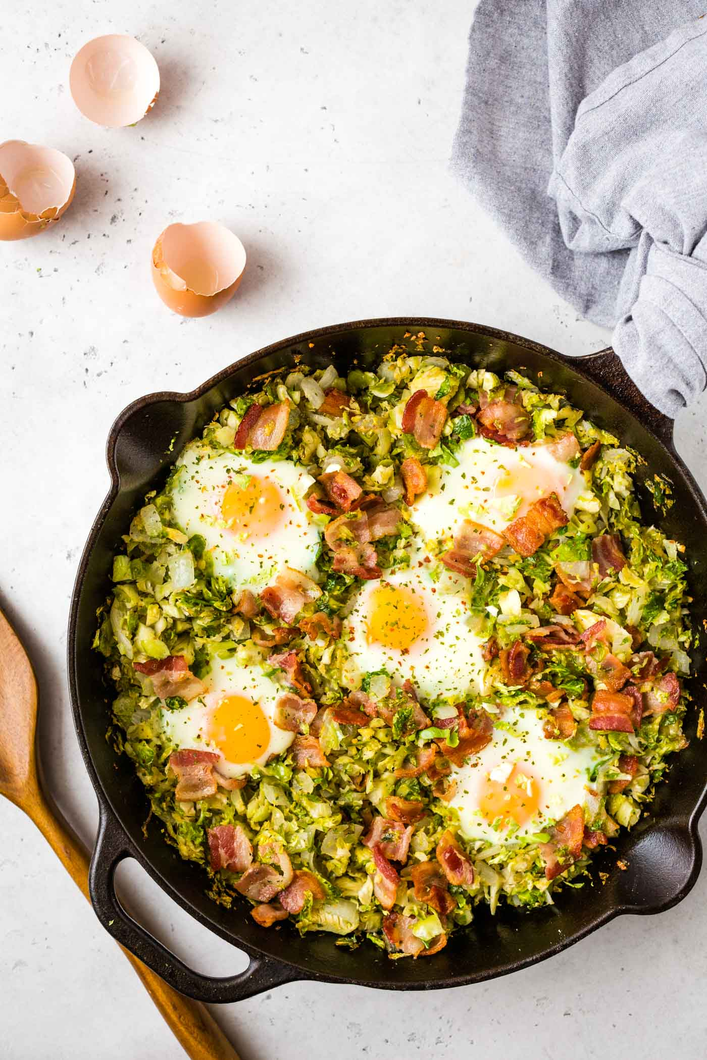 Shredded Brussels sprouts, bacon, and runny eggs in cast iron skillet