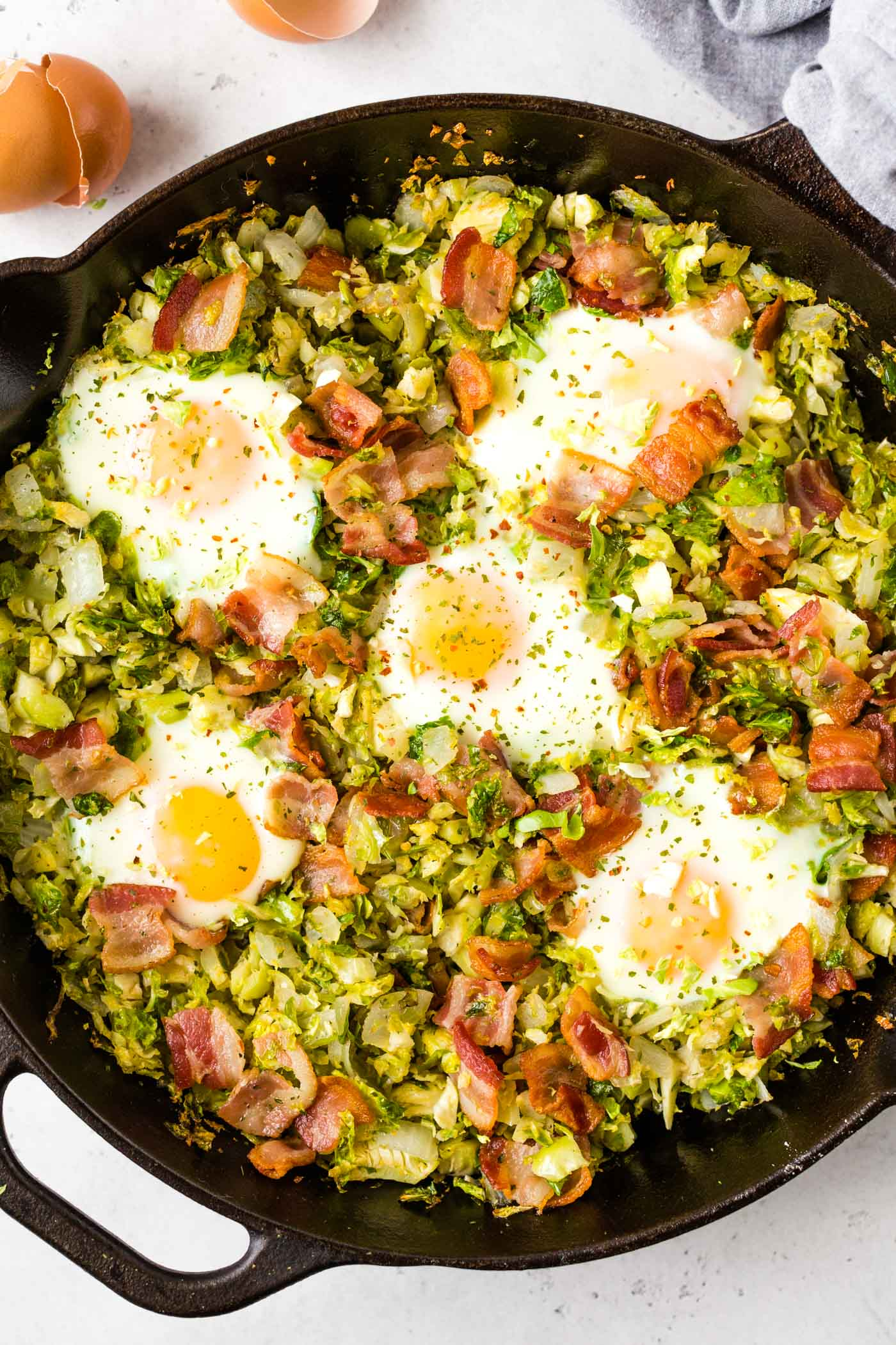 Overhead shot of Brussels sprouts hash with bacon and fried eggs on top