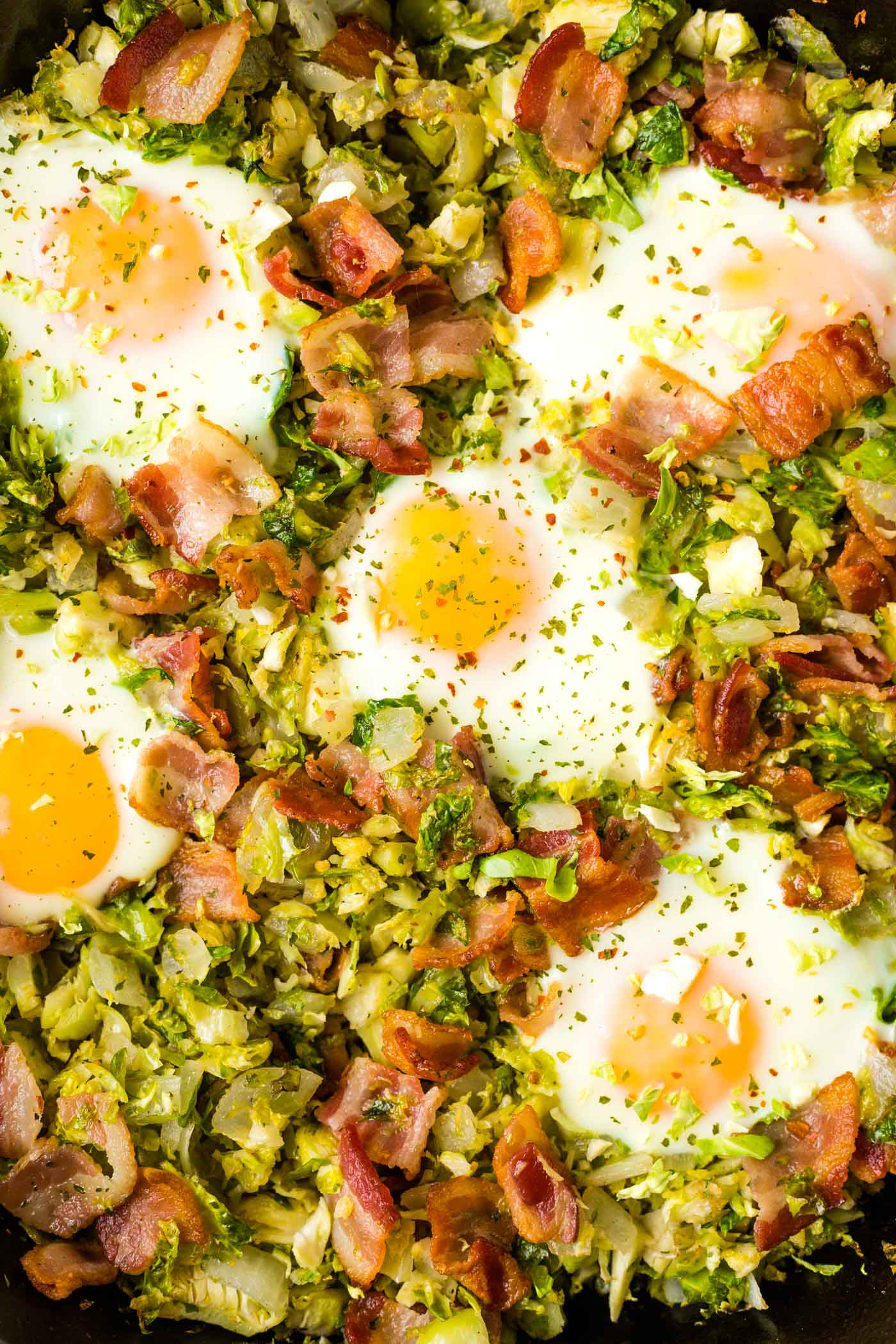 Close-up shot of shredded Brussels sprouts, crispy bacon, and runny eggs