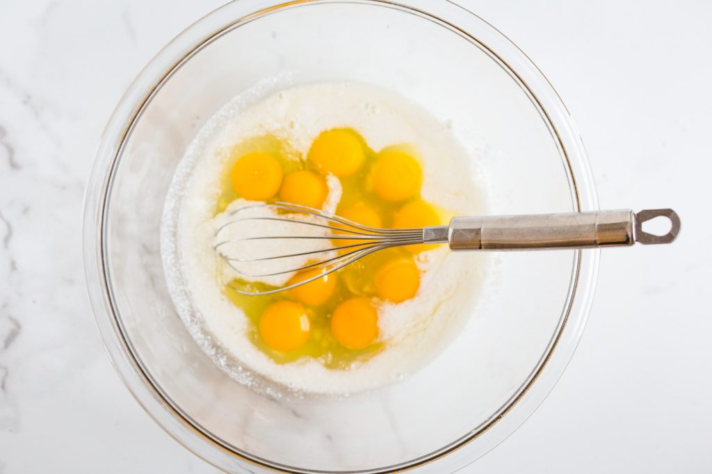Cracked eggs and coconut milk in glass bowl with whisk